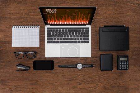 top view of workplace with arranged empty textbook, smartphone, wristwatch and laptop with online trade on screen