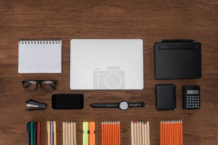 top view of workplace with arranged pencils, empty textbook, smartphone and laptop on wooden table