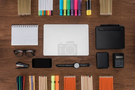 Photo for Top view of workplace with arranged laptop, smartphone, calculator and colorful pencils on wooden table - Royalty Free Image