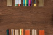 top view of arranged colorful pencils and markers on wooden table
