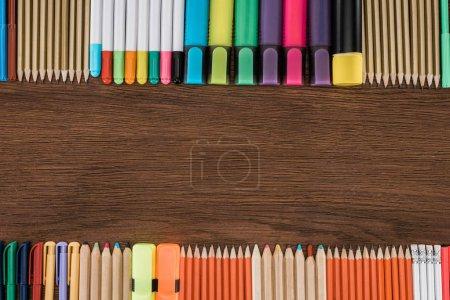 Foto de Vista elevada de marcadores y lápices de colores dispuestos en la mesa de madera - Imagen libre de derechos