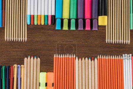 Foto de Lay Flat con lápices de colores dispuestas y marcadores en la mesa de madera - Imagen libre de derechos