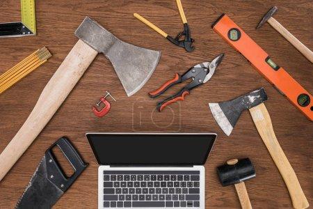 Photo pour Vue du dessus de l'ordinateur portable avec écran blanc entouré de divers outils sur la table en bois - image libre de droit