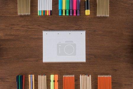 Photo pour Vue de dessus du vide manuel près disposés divers crayons et marqueurs sur table en bois - image libre de droit