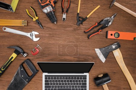 Photo for Top view of laptop with blank screen surrounded by arranged various tools on wooden table - Royalty Free Image