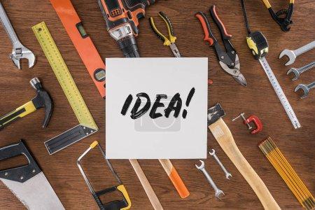 Photo pour Vue de dessus du papier avec lettrage idée près disposés divers outils sur table en bois - image libre de droit