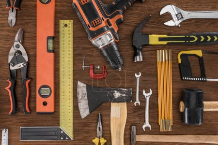 Photo for Top view of axe, electric drill, spirit level, hammers and various tools on wooden table - Royalty Free Image