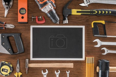top view of empty blackboard near arranged various tools on wooden table