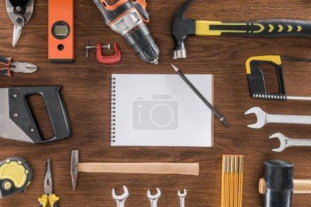 Foto de Vista superior del libro de texto vacío rodeado por arregló varias herramientas en mesa de madera - Imagen libre de derechos
