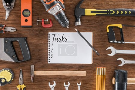 Photo for Top view of textbook with lettering tasks near various tools on wooden table - Royalty Free Image