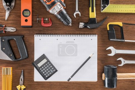 top view of empty textbook, calculator and pencil surrounded by arranged various tools on wooden table