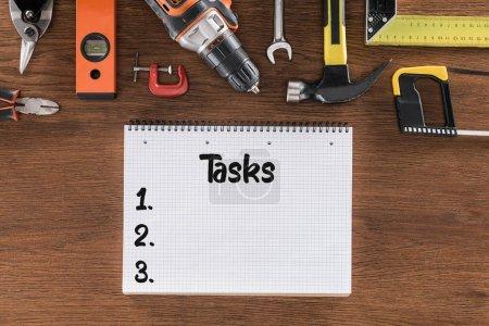 Photo pour Vue de dessus du manuel avec lettrage des tâches près de divers outils sur table en bois - image libre de droit