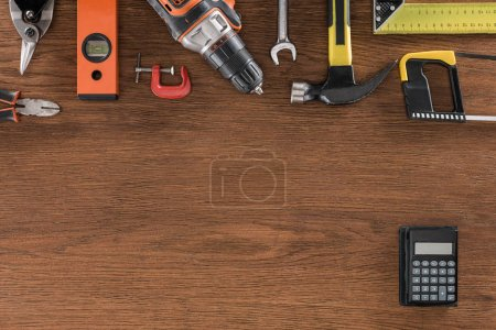 top view of arranged various tools and calculator on wooden table