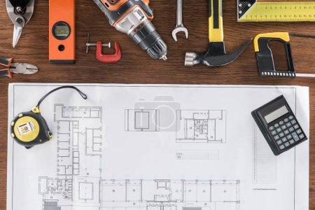 Photo pour Vue de dessus du plan de l'architecte, mesure de ruban, calculatrice et divers outils sur la table en bois - image libre de droit