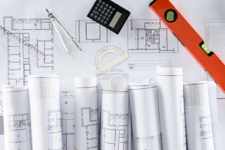 Photo for Top view of architect blueprints, ruler, protractor, calculator, divider and spirit level - Royalty Free Image