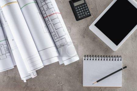 Ansicht des Architekten-Arbeitsplatzes mit leerem Lehrbuch, Taschenrechner und digitalem Tablet mit leerem Bildschirm