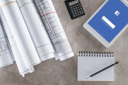 Ansicht des Architekten-Arbeitsplatzes mit leerem Lehrbuch, Taschenrechner und digitalem Tablet mit Facebook auf dem Bildschirm