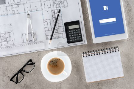 top view of architect workplace with blueprint, divider, coffee and digital tablet with facebook on screen