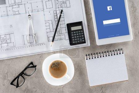 Foto de Vista superior del trabajo del arquitecto con planos, divisor, café y tableta digital con facebook en la pantalla - Imagen libre de derechos