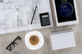 top view of architect workplace with blueprint, divider, coffee and ipad tablet on table