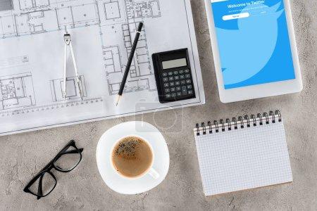 Photo pour Vue de dessus du travail d'architecte avec blueprint, diviseur, café et tablette numérique avec twitter sur l'écran - image libre de droit