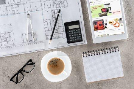 Foto de Vista superior del trabajo del arquitecto con planos, divisor, café y tableta digital con ebay en pantalla - Imagen libre de derechos