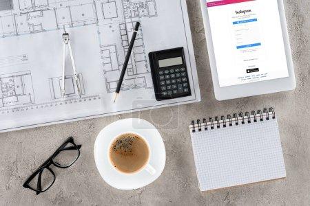 Photo pour Vue de dessus du travail d'architecte avec blueprint, diviseur, café et tablette numérique avec instagram sur écran - image libre de droit