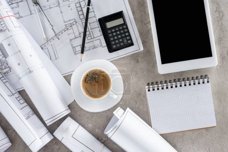 top view of architect workplace with coffee cup, blueprints, calculator and digital tablet with blank screen