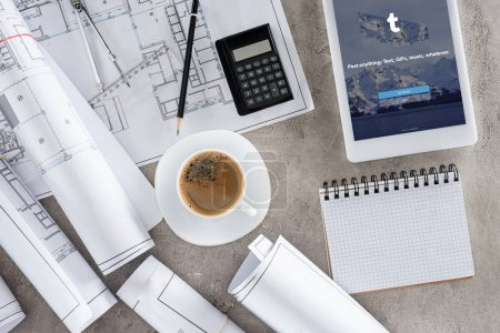 top view of architect workplace with coffee cup, blueprints, calculator and digital tablet with tumblr on screen