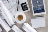 vue de dessus du travail d'architecte avec une tasse de café, bleus, calculatrice et tablette numérique avec tumblr sur écran