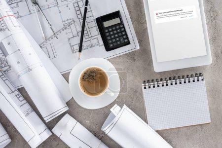 Foto de Vista superior del trabajo del arquitecto con la taza de café, planos, calculadora y tableta digital con la página bloqueada de vk.com en pantalla - Imagen libre de derechos