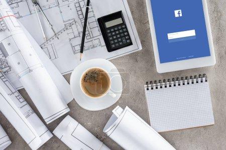 Photo pour Vue de dessus du travail d'architecte avec une tasse de café, bleus, calculatrice et tablette numérique avec facebook sur écran - image libre de droit