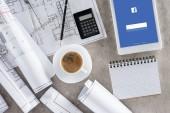 vista superior del trabajo del arquitecto con la taza de café, planos, calculadora y tableta digital con facebook en la pantalla