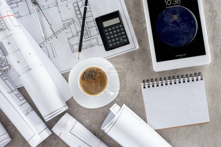 top view of architect workplace with coffee cup, blueprints, calculator and ipad tablet on table