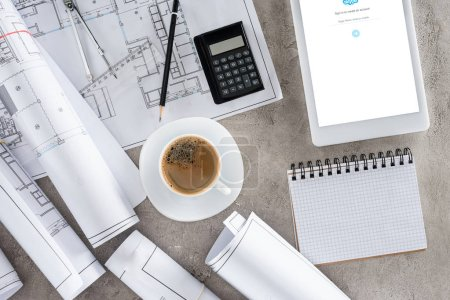 top view of architect workplace with coffee cup, blueprints, calculator and digital tablet with skype on screen