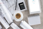 vista superior del trabajo del arquitecto con la taza de café, planos, calculadora y tableta digital con Skype en la pantalla