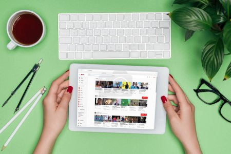 Photo for Cropped image of female architect holding digital tablet with youtube on screen at table with divider, coffee and potted plant - Royalty Free Image
