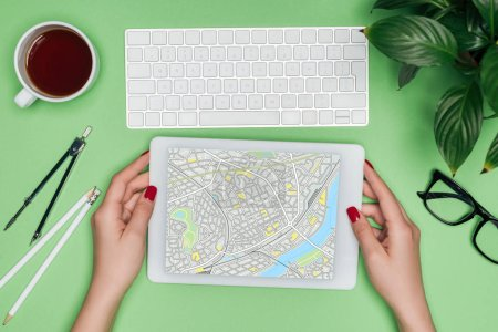 cropped image of female architect holding digital tablet with map on screen