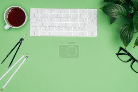 top view of architect workplace with computer keyboard, divider and coffee cup on green table