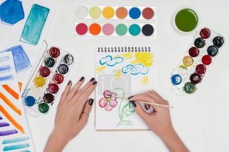 Foto de Imagen recortada de la mujer artista de dibujo de paintbrush en libro de texto en una tabla blanca con pinturas de colores - Imagen libre de derechos