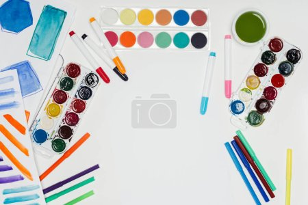 top view of artist workplace with colorful paints and markers on white table