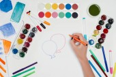 cropped image of female artist drawing air balloons at white table with colorful paints