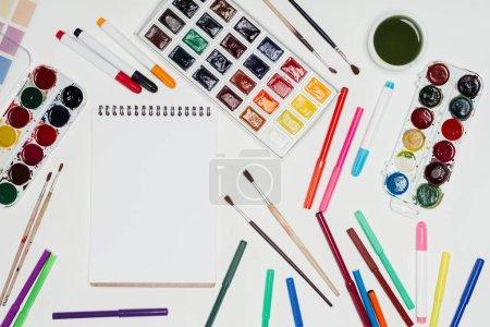 Photo pour Vue de dessus du lieu de travail de l'artiste avec manuel vide, pinceaux, peintures colorées et marqueurs - image libre de droit