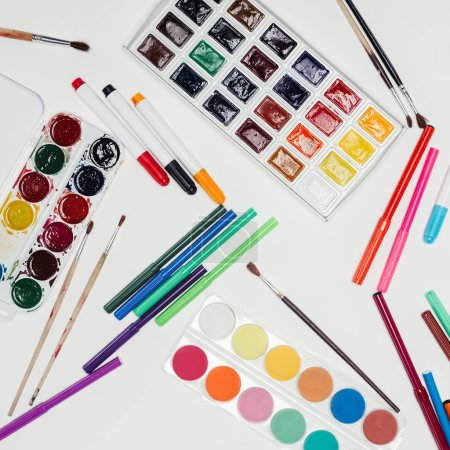 top view of paintbrushes, colorful pants and markers on white table