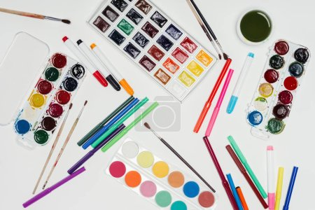 top view of colorful paints, paintbrushes and markers on white table