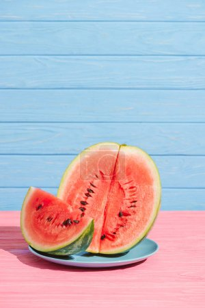 close up view of cut juicy watermelon on plate on pink tabletop on blue backdrop
