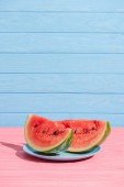 close up view of juicy watermelon slices on plate on blue backdrop
