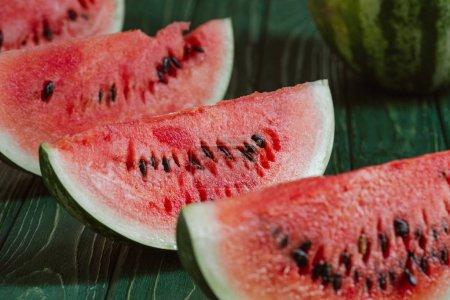 Photo pour Bouchent la vue de tranches de melon d'eau sur une surface en bois verte - image libre de droit