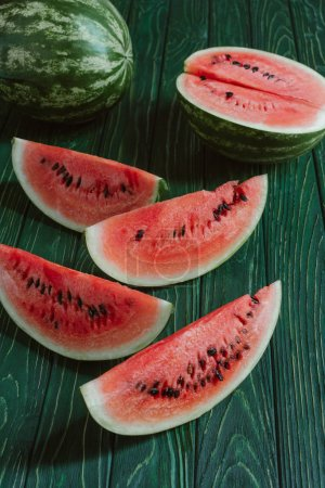 close up view of watermelon slices on green wooden surface