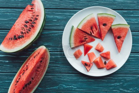 flat lay with fresh watermelon pieces on plate on blue wooden tabletop